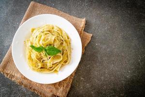 pâtes fettuccine au pesto avec du parmesan sur le dessus - style cuisine italienne photo