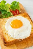 pain maison grillé avec du fromage et un œuf au plat sur le dessus avec une salade de légumes pour le petit-déjeuner photo