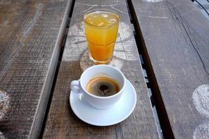 tasse de café et un verre de jus d'orange frais sur une planche en bois photo