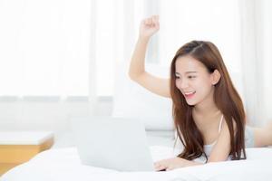 jeune femme asiatique se détendre et se détendre avec un ordinateur portable sur le lit photo