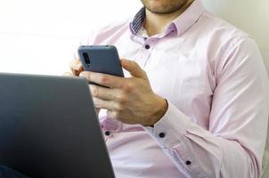 un homme en chemise et jean résout les problèmes de travail à distance. photo