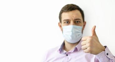 un homme en chemise dans un masque de protection. montrant les pouces vers le haut. photo