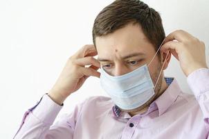 un homme en chemise met un masque. protection antivirus. photo