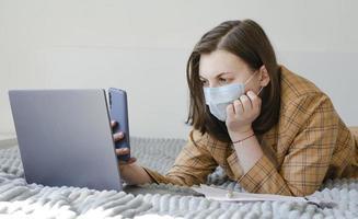 une femme d'affaires résout les problèmes de travail à distance. ordinateur portable et téléphone. photo