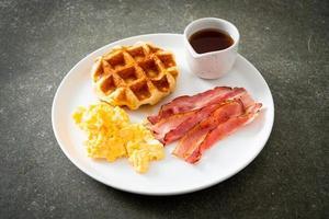 oeuf brouillé avec bacon et gaufre pour le petit déjeuner photo