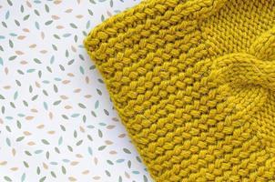 casquette à la main. fond tricoté. texture tricotée. photo