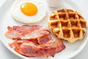 oeuf au plat avec bacon et gaufre pour le petit déjeuner photo