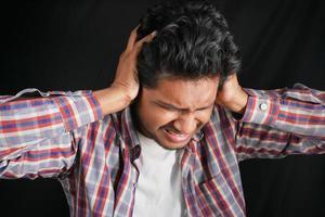 jeune homme ayant des douleurs à l'oreille touchant son oreille douloureuse isolée sur fond noir photo