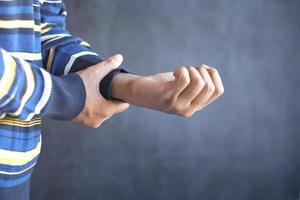 homme souffrant de douleur à la main sur fond noir photo