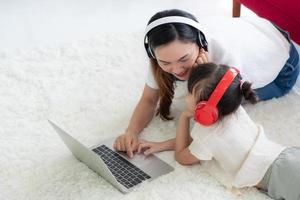 mère asiatique avec enfant enseignant à étudier à partir d'un ordinateur à la maison photo