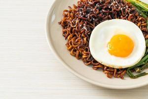 nouilles instantanées séchées faites maison à la sauce noire épicée coréenne avec œuf au plat et kimchi photo