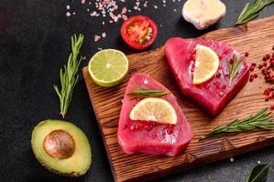 steaks de filet de thon frais aux épices et herbes sur fond noir photo