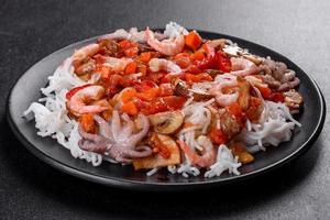 savoureuses nouilles de riz avec tomate, poivron rouge, champignons et fruits de mer photo