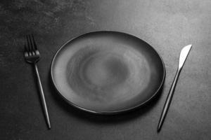 couverts noirs sur une table sombre en béton. table à manger photo