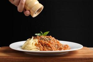 main tenant un moulin à poivre avec des spaghettis et de la sauce rouge dans un plat blanc photo