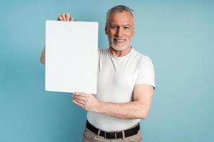 retraité souriant avec une barbe tenant une feuille de papier vierge photo