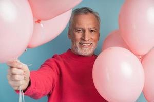 homme souriant et gai avec des ballons photo