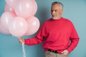 un homme aux cheveux gris et à la barbe tient des ballons roses photo