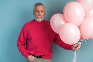 bouleversé, un homme barbu plus âgé porte, tenant des ballons à la main photo