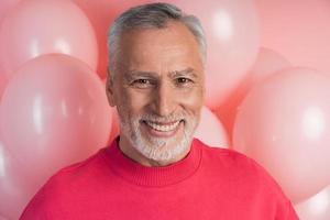 homme sincère et séduisant souriant sur fond de ballons roses photo