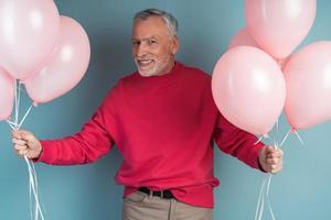 photo d'un homme senior séduisant tenant des ballons roses