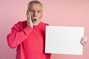 surpris senior man tenant une feuille de papier blanc. isolé photo