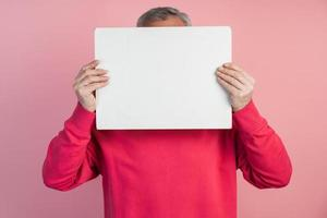 l'homme se couvre le visage d'une feuille de papier blanc photo