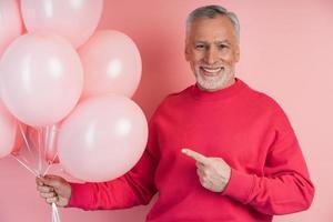 homme senior souriant tenant des ballons sur fond rose photo