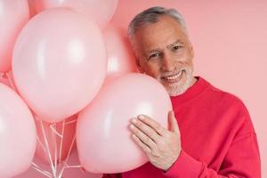 homme positif et joyeux avec des ballons posant sur fond de mur rose photo
