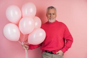 homme heureux célébrant la tenue de ballons roses photo
