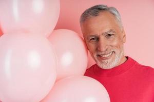 homme âgé aux cheveux gris et à la barbe et aux ballons roses photo