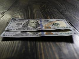 Billets de deux cents dollars sur un fond en bois photo