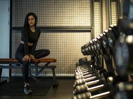fille brune en haut noir et leggings est assise sur un banc photo