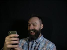 homme élégant avec une barbe et une moustache se penche sur un téléphone mobile photo