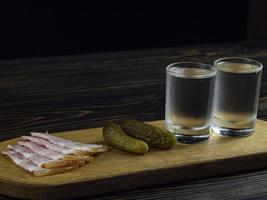 deux verres embués avec de la vodka froide sur une planche de bois photo