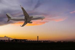 avion commercial survolant l'aéroport au coucher du soleil photo