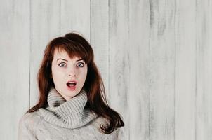 fille dans un pull gris, grands yeux surpris, bouche ouverte photo