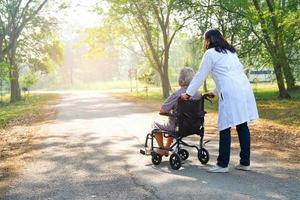 aider et soutenir une patiente asiatique assise sur un fauteuil roulant au parc. photo