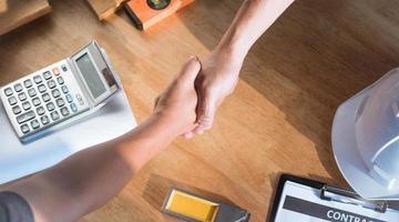 vue de dessus de l'architecture et de l'ingénieur se serrant la main sur la table de travail photo