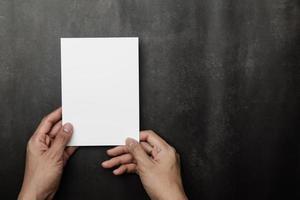 main tenant une maquette de carte d'invitation, modèle de carte de voeux vierge photo
