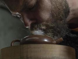 l'homme avec une barbe respire de la fumée dans une théière traditionnelle photo