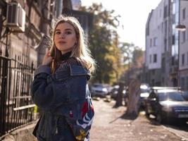 belle fille blonde se tient dans une vieille ruelle dans une veste en jean photo