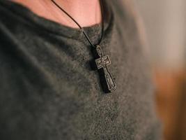 croix orthodoxe en bois accrochée au cou d'un homme photo