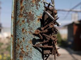 vis rouillées sur l'aimant sur le poteau de fer dans la rue photo