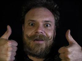 visage drôle d'un homme avec une barbe et une moustache montrant les pouces vers le haut photo