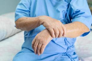 Une patiente asiatique âgée ressent de la douleur au poignet et au bras photo