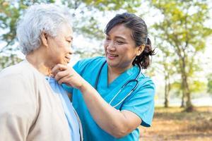 aide de médecin et soins femme senior asiatique marchant au parc photo