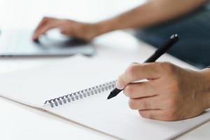 les mains du jeune homme écrivent sur le bloc-notes, le bloc-notes et utilisent un ordinateur portable photo