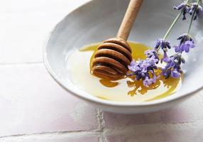 bol avec du miel et des fleurs de lavande fraîche photo