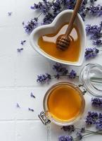 pot et bol avec du miel et des fleurs de lavande fraîches photo